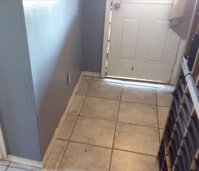 Water damage to the floor in the front entry of house