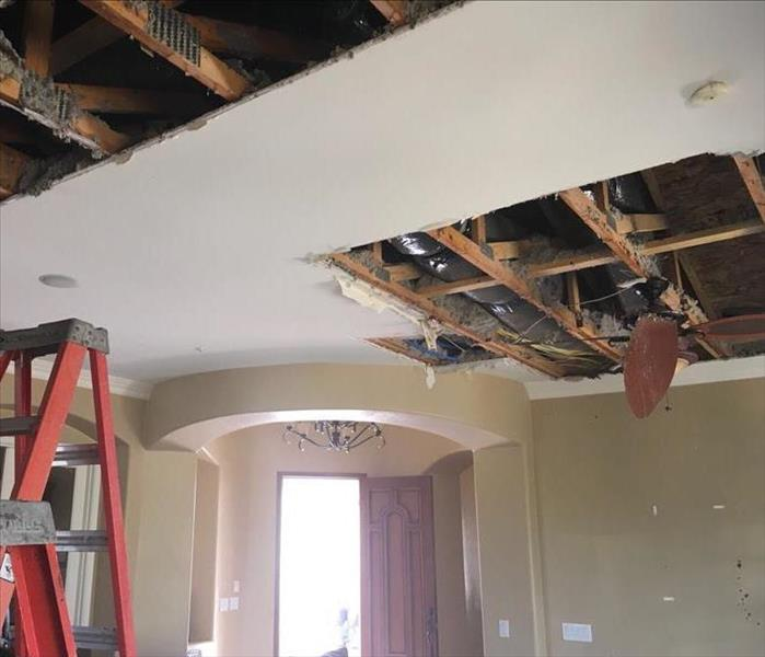 Holes in ceiling of living room after extensive water damage