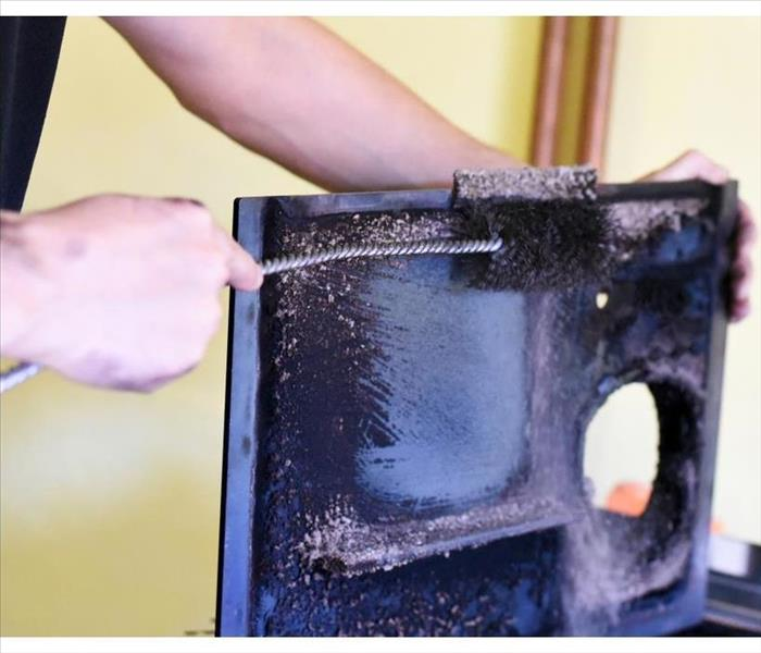 Man cleaning wood burning stove.